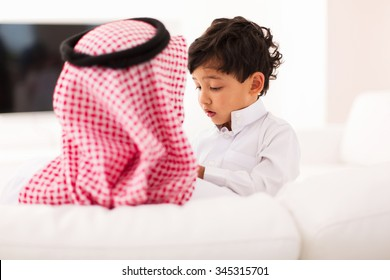 little muslim boy and his father spending time together at home