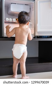 Little naked baby boy looking for something in refrigerator.