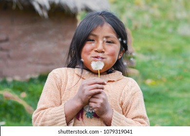 Little native american girl blowing dandelion flower.
