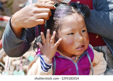 Little native american kid feeling pain because of brushing her hair.