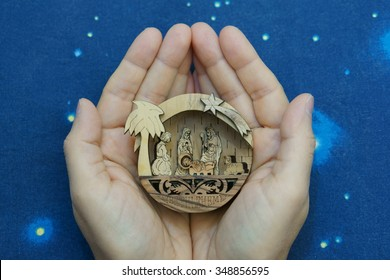 Little nativity scene (carved in wood) in the hands on blue sky background