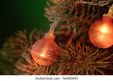 Little New Year tree decorated with electric garland with small red balls on a dark green background.