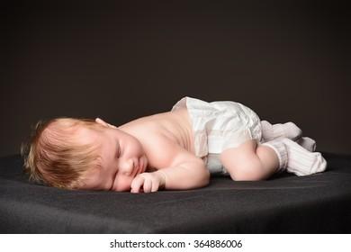 Little newborn baby asleep. Black background.