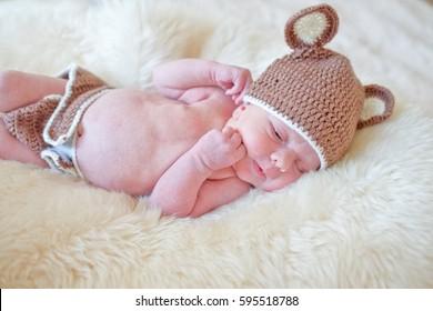 LIttle newborn baby boy laying on the fur wearing crochetting bear hat.