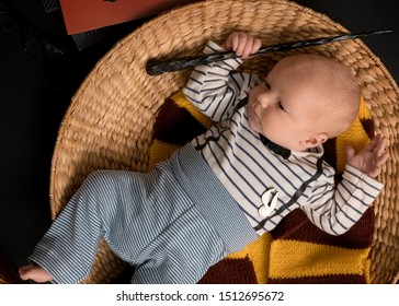 Little newborn baby boy like in a magic book in halloween time. Magic wand, black background and scarf