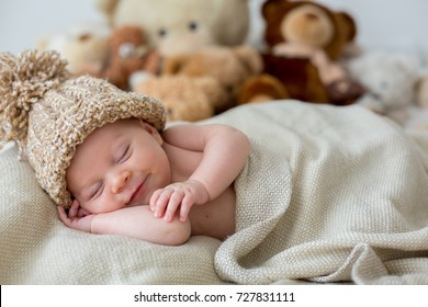 Little newborn baby boy, sleeping with teddy bear at home in bed, infant resting with toy