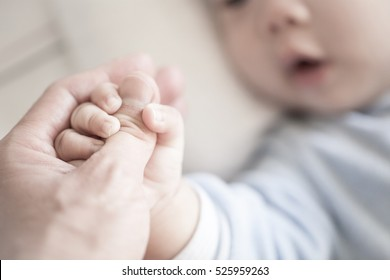 Little newborn baby holding parent's one hand, close-up macro shot. Focus on foreground. The touching and lovely moment. Concept of support, hope, love, bonding and care, hold on...