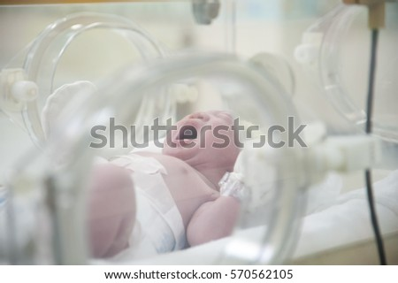 Little Newborn baby in incubator. Adorable infant in yellow hats wrapped in blue cloth in delivery room.