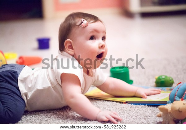 Little newborn baby lying on the floor and playing with toy