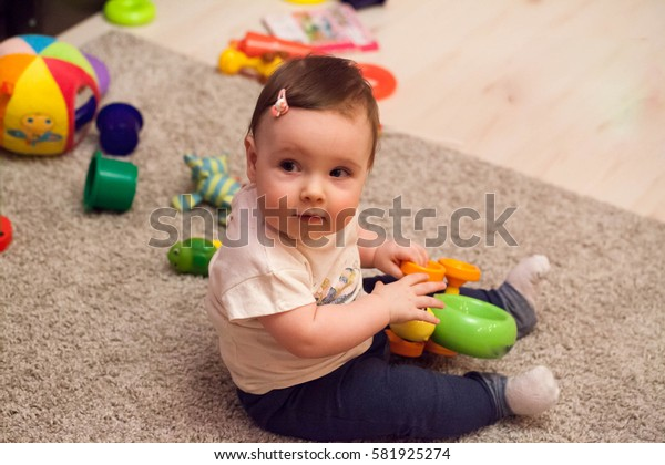 Little newborn baby seat on the floor and playing with toy car