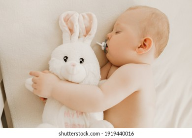 Little newborn baby sleeping with plush toy-white hare in the crib