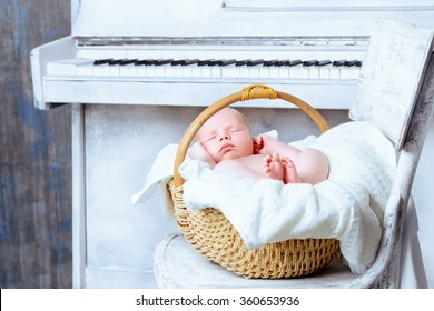 Little newborn baby sleeps next to a white piano. Vintage style. Music, art concept.