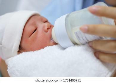 little newborn baby sucking milk in bottle