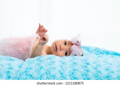 little newborn girl  lie down on light blue blanket, lift her hand up and looking to her mother on white background