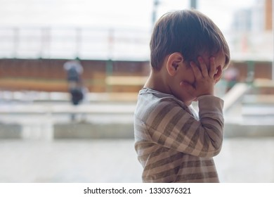 a little offended boy closes his face with his hands. The concept of child bullying, domestic violence, child abuse