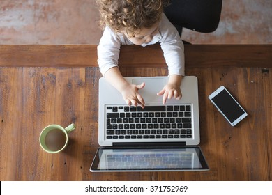 Little office worker. Toddler playing with laptop on wooden table