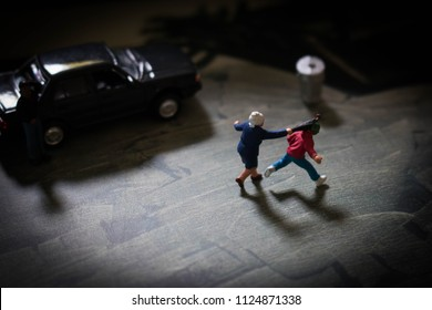 Little old lady fights back after being mugged by a young thug, Woman hits man with umbrella in self defence, Brave granny won't give up her purse. Crime concept depicted using miniature people.