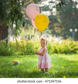 little one year old baby girl in a dress with balloons