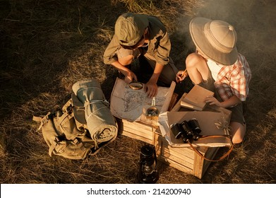 Little ones - boy and girl - studying the map of the area and the upcoming campaign at sunset