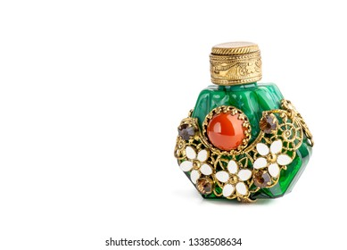 Little oriental perfume bottle in green jade, with brown sinhalite gems and red carnelian stone, ornate with brass filigree and white  porcelain enamel flowers. Isolated on white background