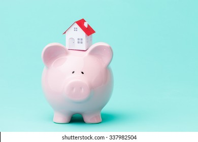 Little paper house on a piggy bank.