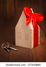 Little paper house with red ribbon and key on wooden background.