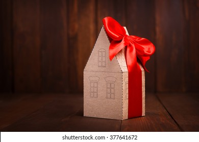 Little paper house with red ribbon on wooden background.