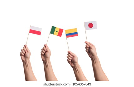 Little paper national flags in hands isolated on white background. Flags of national football teams of Poland, Senegal, Columbia, Japan. World cup competitors in group H