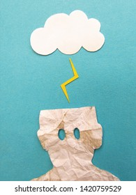 Little papercut man is electrocuted by a lightning. Rain of ideas. Electrocuted papercut.