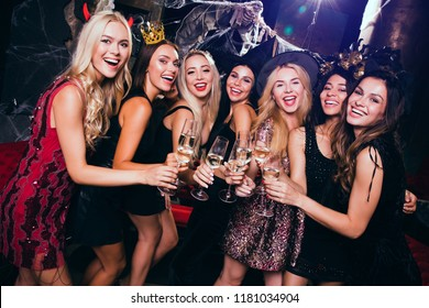 Little party never killed nobody! Beautiful young women in evening gown looking at camera and drinking champagne with smile while celebrating Halloween in nightclub