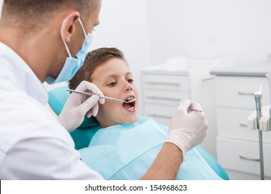 Little patient at dentist office. Little boy sitting at the chair in dental office while doctor examining teeth