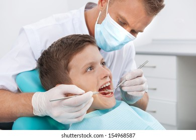 Little patient at dentist office. Side view of little boy sitting at the chair at the dental office while doctor examining teeth