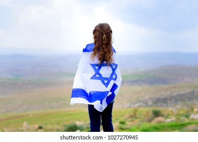 Little patriot jewish girl standing and  enjoying great view on the sky, spring field and mountains with the flag of Israel wrapped around her. Memorial day-Yom Hazikaron and Yom Ha'atzmaut concept.