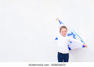 Little patriot jewish girl standing  and enjoying with the flag of Israel on white wall background.Memorial day-Yom Hazikaron, Patriotic holiday Independence day Israel - Yom Ha'atzmaut concept.