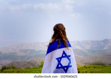 Little patriot jewish girl standing and  enjoying great view on the sky, spring field and mountains with the flag of Israel wrapped around her. Memorial day-Yom Hazikaron and Yom Haatzmaut concept.