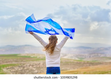 Little patriot jewish girl standing  and enjoying with the flag of Israel on blue sky background.Memorial day-Yom Hazikaron, Patriotic holiday Independence day Israel - Yom Ha'atzmaut concept