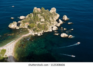Little peninsula, Isola Bella, people at the beach, small boats around, blue sea in Taormina, Sicily, Italy
