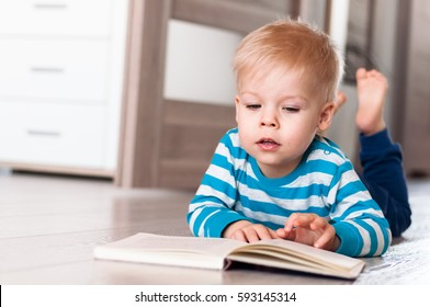 Little, pensive, lost in thought, two years old boy lying on his belly on the floor, with open book in front of him, shows something finger on page.