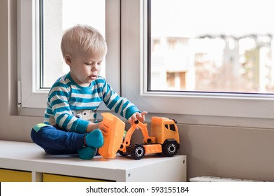 Little, pensive, two years old boy sitting by the window and playing with toy truck