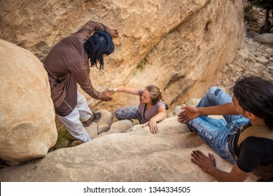 LITTLE PETRA, JORDAN - AUGUST 14, 2016: unidentified young turist beeing helped to climb a rock in Little Petra, Jordan, by local people