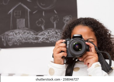 Little photographer. / Mixed child taking photos in a playroom with blackboard background