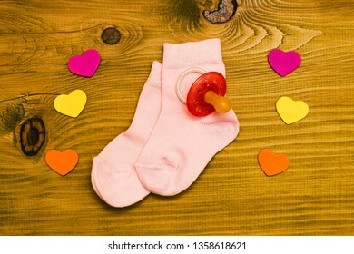 Little pink baby girl socks with pacifier and heart shapes on wooden table.Baby announcement concept.Toned photo.
