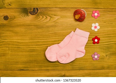 Little pink baby girl socks with pacifier and flowers on wooden table.Baby announcement concept.Toned photo.