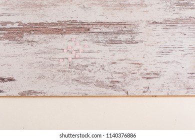 little pink beads lie on a white rough old wooden board