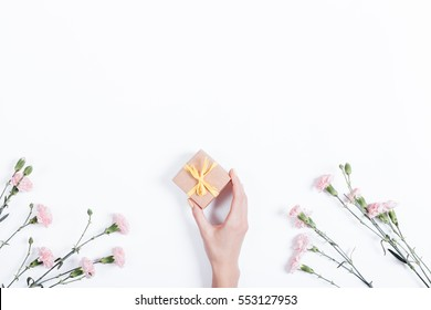 Little pink carnation on a white background and a woman's hand with a gift in a small box, space for text, top view