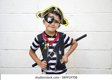 Little pirate boy is posing to the camera while his hands on waist. Rustic wall background.