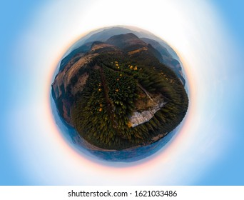 Little planet aerial view of the Recreation Mountain Pysany kamin in Carpathian mountains. autumn. Pine forest, houses on the peaks, yellow fields and trees. Mountain meadow. sunset, Ukraine
