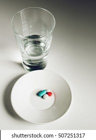 Little plate with medical pills and a glass with water over white table