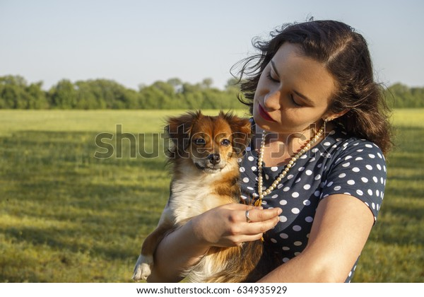 Little playful dog in the arms of a girl
