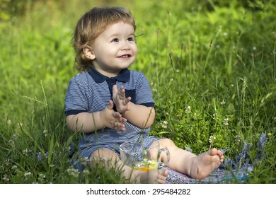 Little playful happy smiling baby boy sitting in field on fresh green grass with glass cup, horizontal picture